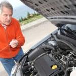 Senior man checking car motor levels — Stock Photo #6700680
