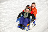Little boy and girl on sleigh winter — Stock Photo