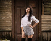 Fashion pretty young woman posing outdoor near a old wooden wall — Stock Photo