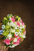 Beautiful bridal bouquet with golden rings in basket — Stock Photo