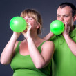 Happy young couple having fun with balloons — ストック写真