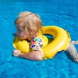 Little baby swimming in a pool on swimming ring — Stockfoto