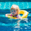 Little baby swimming in a pool on swimming ring — Stock fotografie