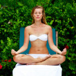 Young woman sitting in lotus position — Stock Photo #18541377