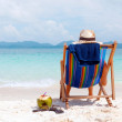 Young woman in hat sitting on tropical beach — Foto de Stock
