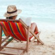 Stockfoto: Young beautiful womsitting on beach reading book