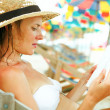 Young beautiful woman sitting on beach reading a book — Stok fotoğraf
