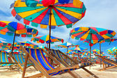 Beach chair and umbrellas on the beach — Stock Photo