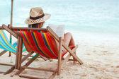 νεαρή όμορφη γυναίκα που κάθεται στην παραλία, διαβάζοντας ένα βιβλίο — Φωτογραφία Αρχείου