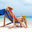 Young woman in hat sitting on tropical beach — Stock Photo