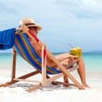 ung kvinna i hatt sitter på tropical beach — Stockfoto