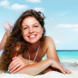 Portrait of a happy young woman posing while on the beach — Stok fotoğraf