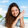 Portrait of a happy young woman posing while on the beach — Stockfoto