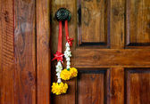 Traditional Thai bouquet hanging on wooden door — Stock Photo