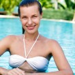 Beautiful young woman posing by the pool in tropical resort — Stock Photo #21717661