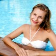 Beautiful young woman posing by the pool in tropical resort — Stock Photo