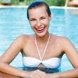 Beautiful young woman posing by the pool in tropical resort — Stock Photo #21717321