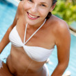 Beautiful young woman posing by the pool in tropical resort - Stock Photo