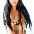 Brunette beautiful model posing on a beach — Stok fotoğraf