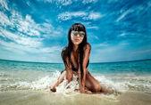Morena hermosa modelo posando en una playa — Foto de Stock