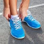 Closeup of Young Woman Tying Sports Shoe — Stock Photo #29153169