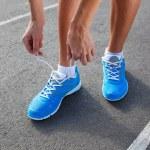 Closeup of Young Woman Tying Sports Shoe — Stock Photo #29153171