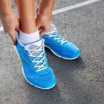 närbild av ung kvinna knyta sport shoe — Stockfoto