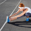 Stock Photo: Female runner stretching before workout.