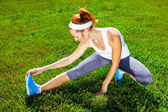 Female runner stretching before workout. — Stock Photo