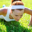 Young woman doing push ups on green grass. — Stock Photo #29871385
