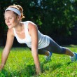 Young woman doing push ups on green grass. — Stock Photo #29871393