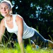 Stock Photo: Young womdoing push ups on green grass.
