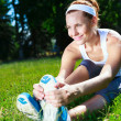 Young girl stretches before exercise in park — Stock Photo