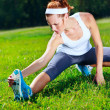 Young girl stretches before exercise in park — Stock Photo #29871437