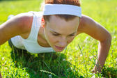 Young woman doing push ups on green grass. — Stock Photo