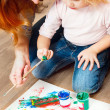 Cute little redhead girl painting. — Stockfoto