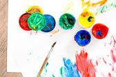 Opened paints with paintbrush on messy paper. — Stockfoto