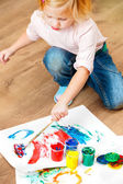 Cute little redhead girl painting. — Stock Photo