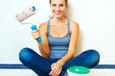 Woman sitting with roller brush ready to work. — Stock Photo