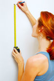 Portrait of young woman with measuring tape. — Stockfoto