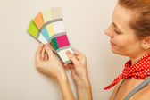 Young beautiful woman holding color palette with color samples. — Stock Photo