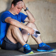 Upset Young male runner resting leaning against wall. — Stock Photo #47288839