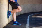 Male runner leaning relaxed against wall.  — Stock Photo