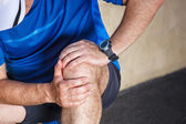 Male runner having problems in knee joint. — Stock Photo