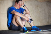 Upset Young male runner resting leaning against wall. — 图库照片