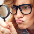 Young geek looking through magnifying glass. — Stock Photo #47831141