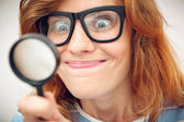 Young geek looking through magnifying glass. — Stock Photo