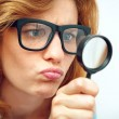 Young geek looking through magnifying glass. — Stock Photo #48081235