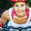 Happy Young woman leaned over the handlebars of her bike. — Stock Photo