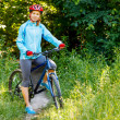 Portrait of happy young woman with mountain bike outdoors. — Stock Photo #48925573